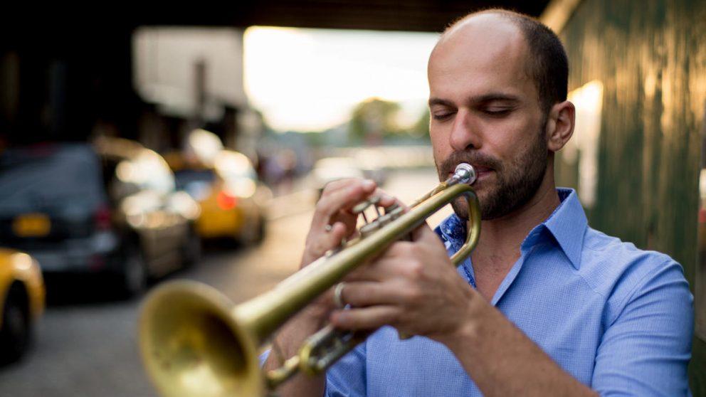 Publicity photo of Amir ElSaffar playing trumpet