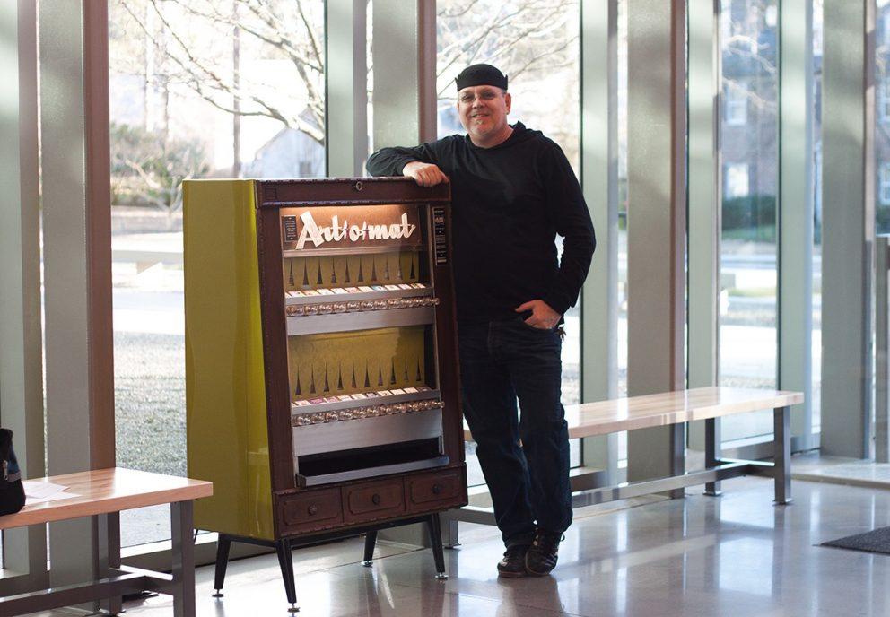 Man leaning against Art o Mat - repurposed cigarette vending machine
